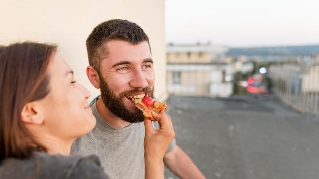 Smiley Couple Manger De La Pizza à L'extérieur Photo Premium