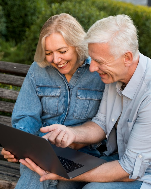 Smiley Couple Plus âgé à L'extérieur Avec Ordinateur Portable Sur Banc Photo gratuit