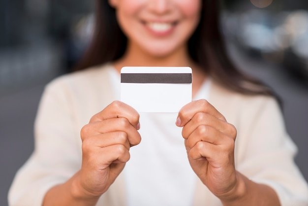 Smiley Defocused Woman Holding Carte De Crédit Photo gratuit