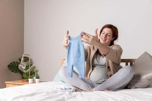 Smiley Enceinte Femme Regardant Des Vêtements De Bébé Photo gratuit