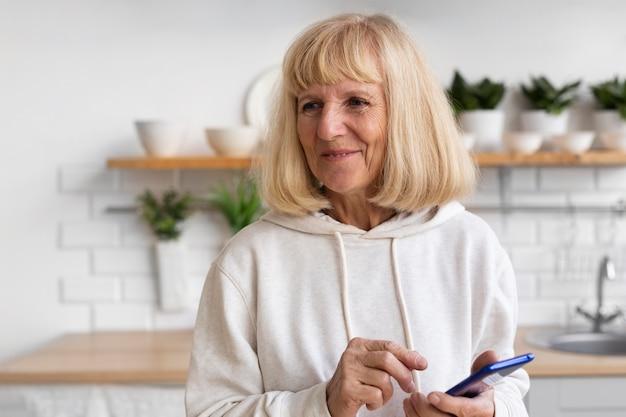 Smiley Femme âgée à L'aide De Smartphone à La Maison Photo gratuit