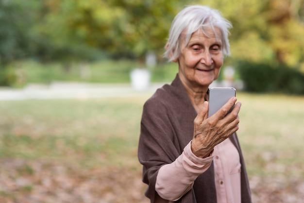 Smiley Femme Aînée Tenant Le Smartphone à L'extérieur Avec Espace De Copie Photo gratuit