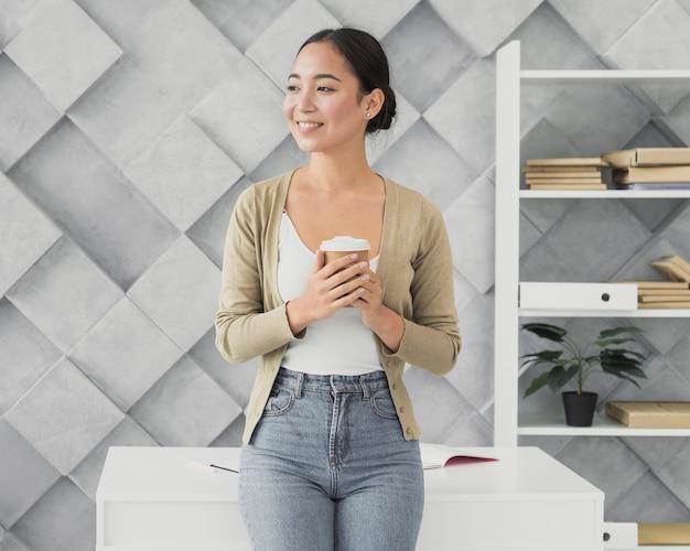 Smiley femme asiatique tenant une tasse de café Photo gratuit