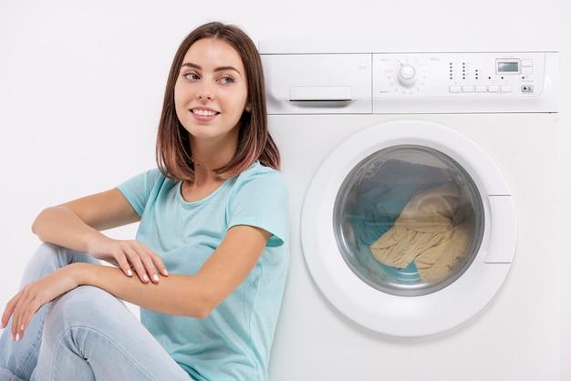 Smiley femme assise près de la machine à laver Photo gratuit