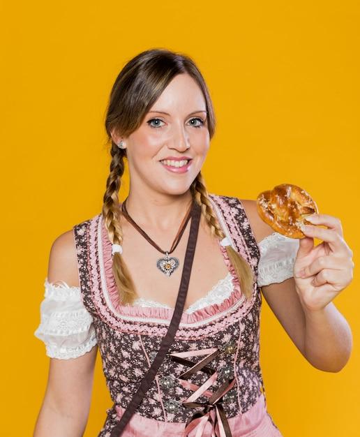 Smiley femme bavaroise avec bretzel Photo gratuit