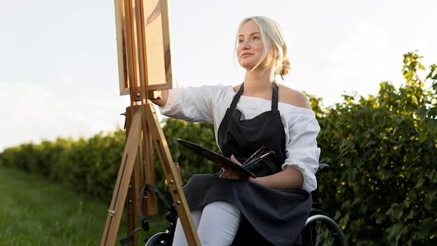 Smiley Femme En Fauteuil Roulant à L'extérieur Dans La Nature Avec Toile Et Palette Photo gratuit