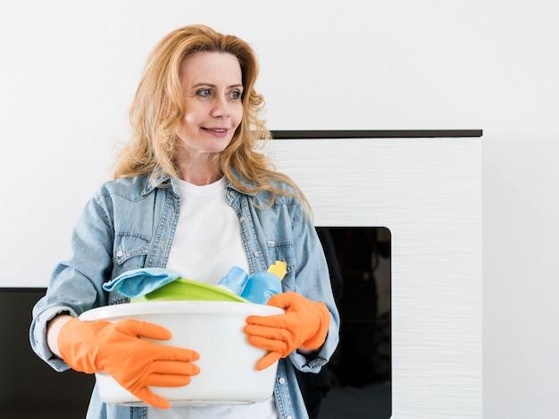 Smiley Femme Avec Des Gants En Caoutchouc Tenant Le Panier De Produits De Nettoyage Photo gratuit