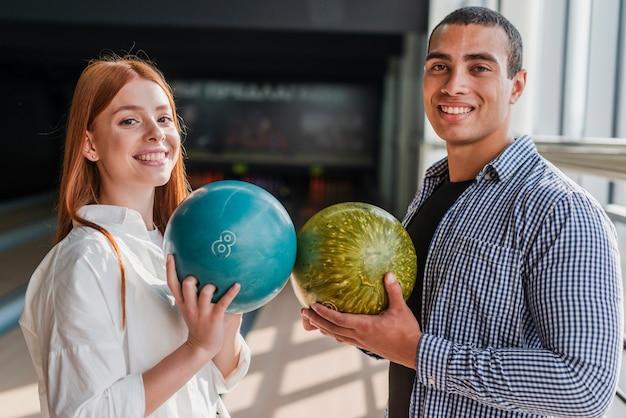 Smiley femme et homme tenant des boules colorées dans un club de bowling Photo gratuit