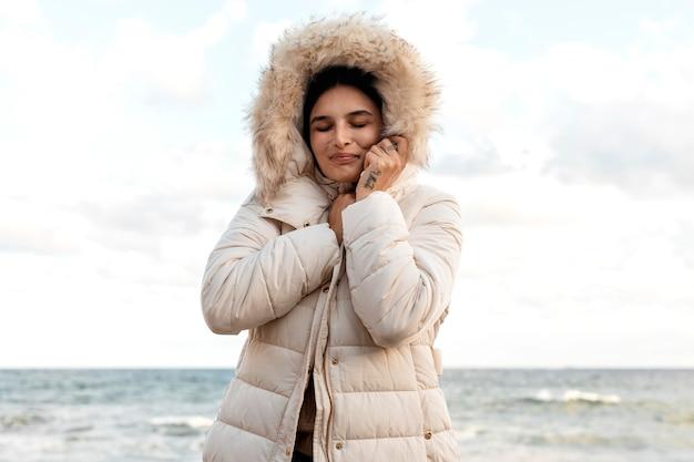 Smiley Femme à La Plage Avec Veste D'hiver Photo gratuit