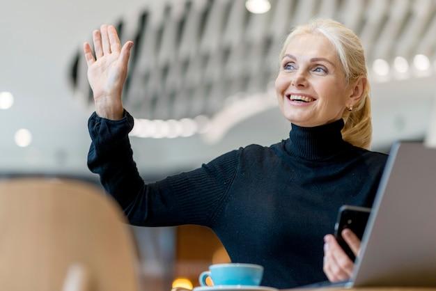 Smiley Femme Plus âgée Demandant La Facture Tout En Travaillant Et En Prenant Un Café Photo gratuit