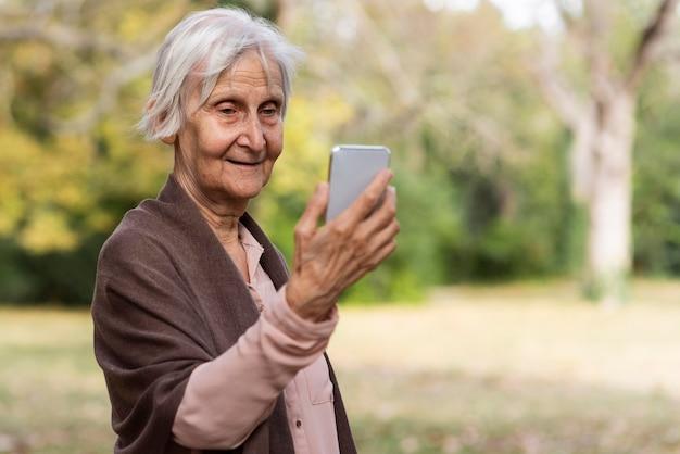 Smiley Femme Plus âgée Tenant Le Smartphone à L'extérieur Photo gratuit