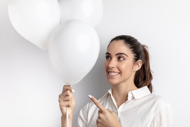Smiley Femme Pointant à Main Ballons Photo gratuit