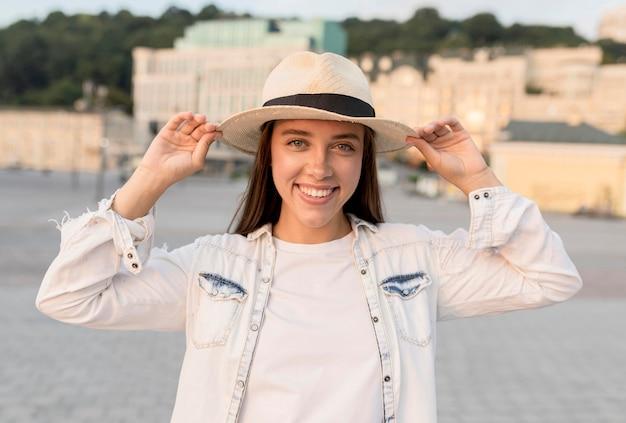 Smiley Femme Posant à L'extérieur Avec Un Chapeau Lors D'un Voyage Photo gratuit