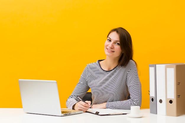 Smiley Femme Posant à Son Bureau Tout En écrivant Quelque Chose Photo gratuit