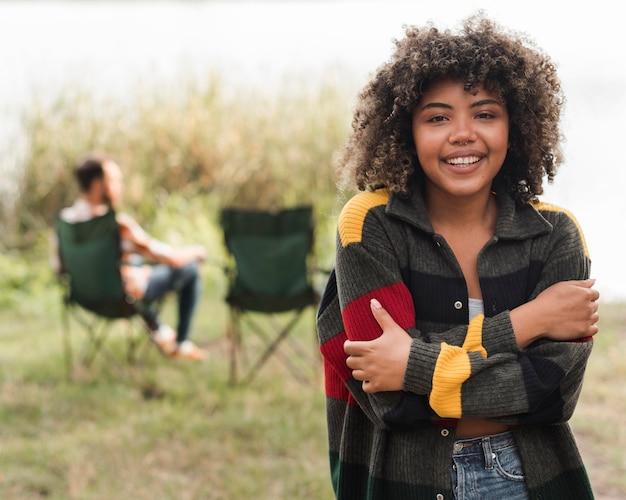 Smiley Femme Posant Tandis Que Petit Ami Se Détendre Sur Une Chaise à L'extérieur Photo gratuit
