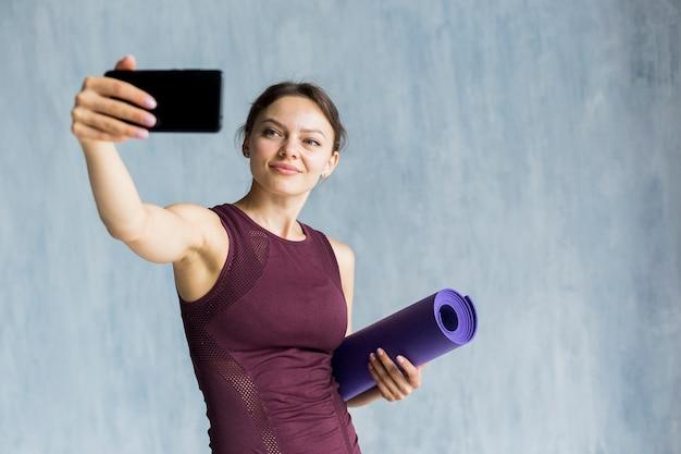 Smiley Femme Prenant Un Selfie Pendant L'entraînement Photo gratuit