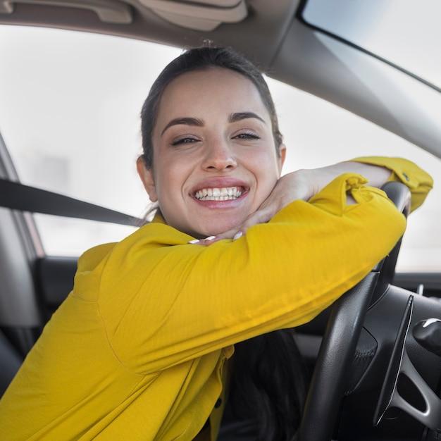 Smiley Femme S'appuyant Sur Le Volant Photo gratuit