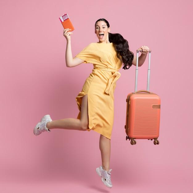 Smiley Femme Sautant Tout En Tenant Ses Bagages Et Passeport Photo gratuit