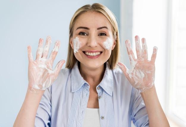 Smiley Femme Se Laver Les Mains Avec Du Savon Photo gratuit