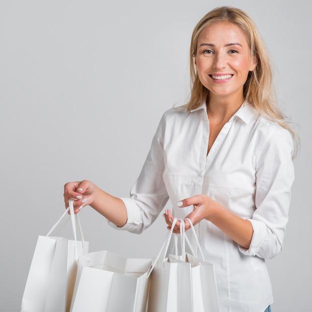 Smiley Femme Tenant Beaucoup De Sacs à Provisions Photo gratuit