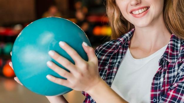 Smiley Femme Tenant Une Boule De Bowling Turquoise Photo gratuit