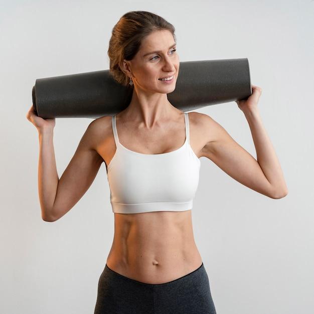 Smiley Femme Tenant Un Tapis De Yoga Photo Premium