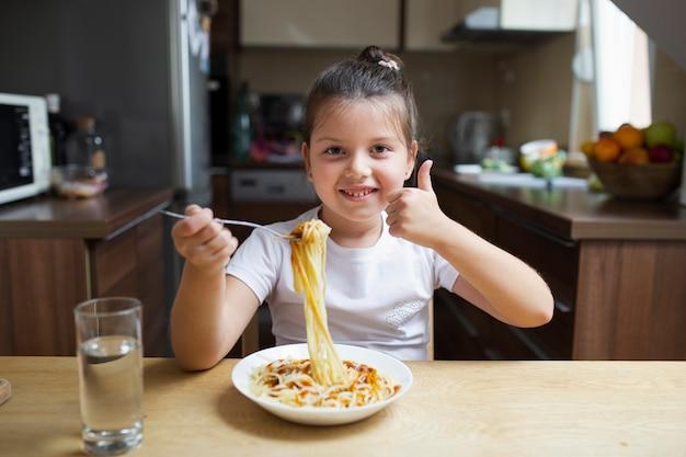 Smiley fille ayant des pâtes au déjeuner Photo gratuit