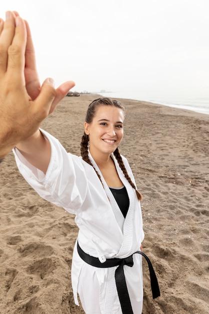 Smiley fille en costume d'arts martiaux en plein air Photo gratuit