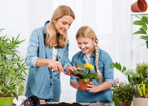 Smiley Fille Et Fille S'occupant Des Fleurs Photo gratuit