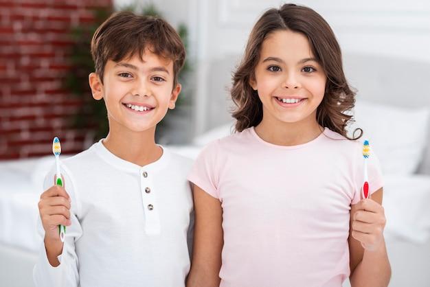 Smiley frères et soeurs à la maison tenant une brosse à dents Photo gratuit