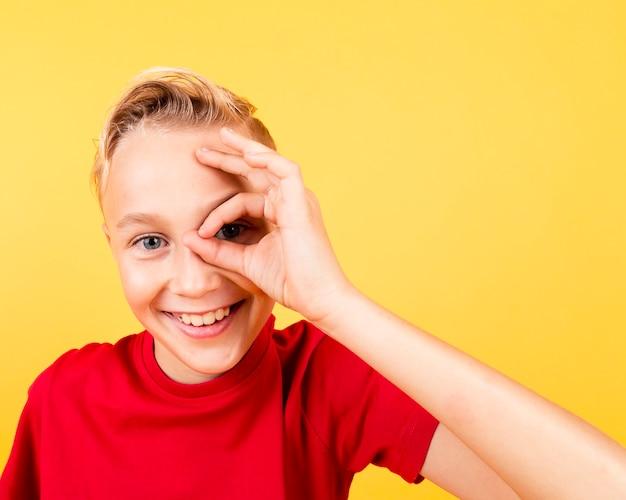 Smiley garçon vue de face couvrant les yeux avec signe ok Photo gratuit