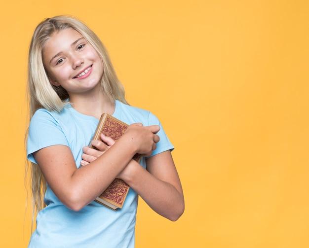 Smiley Girl Holding Book Photo gratuit