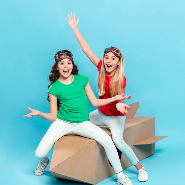 Smiley Girls Sitting On Cartoon Flying Ship Photo gratuit