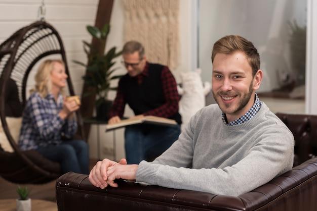 Smiley Homme Posant Sur Un Canapé Avec Des Parents Défocalisés Photo gratuit