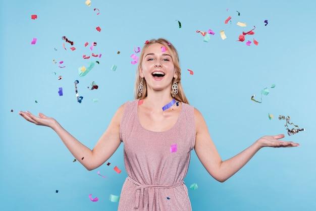 Smiley jeune femme jetant des confettis Photo gratuit