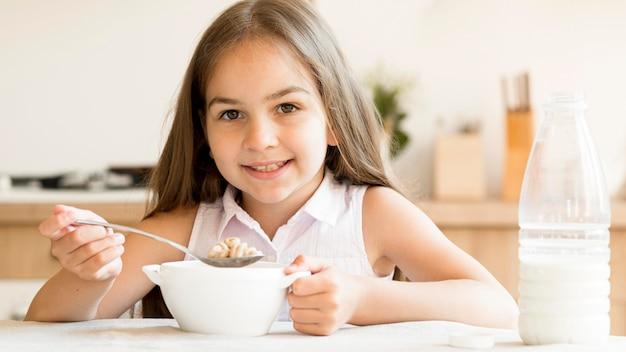 Smiley Jeune Fille Mangeant Des Céréales Pour Le Petit Déjeuner Photo gratuit