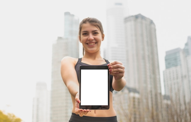 Smiley jeune fille tenant la tablette Photo gratuit