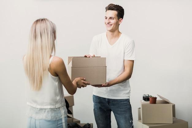 Smiley jeune homme et femme tenant une boîte Photo gratuit