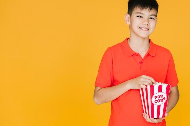 Smiley kid ayant pop-corn avec espace de copie Photo gratuit