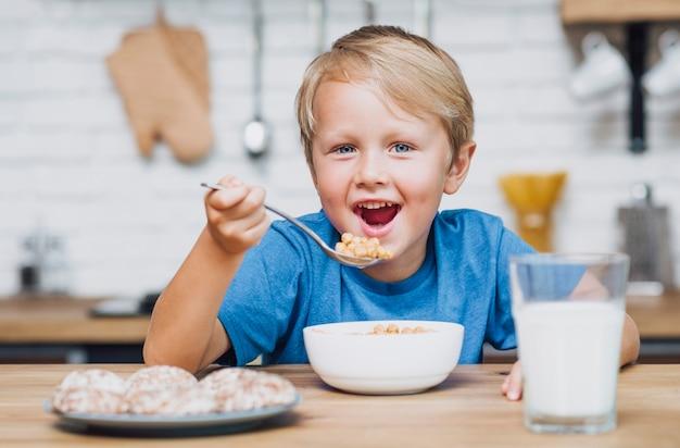 Smiley kid manger des céréales Photo gratuit