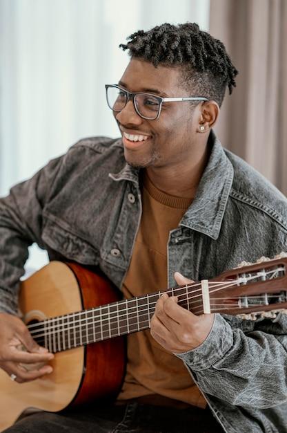 Smiley Musicien Masculin à La Maison à Jouer De La Guitare Photo gratuit