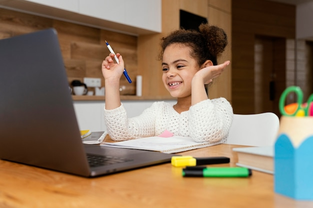 Smiley Petite Fille à La Maison Pendant L'école En Ligne Photo gratuit