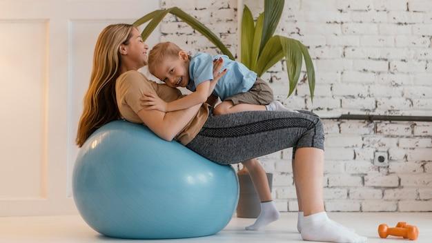 Smiley Plein Coup Femme Et Enfant Sur Ballon De Gym Photo gratuit
