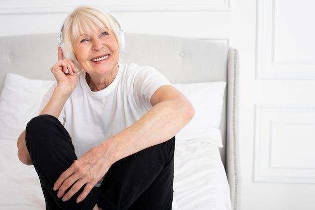 Smiley senior avec un casque Photo gratuit
