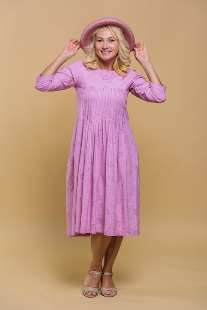 Smiley senior femme posant dans une robe rose Photo gratuit