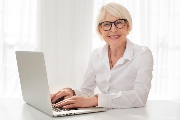 Smiley senior travaillant sur un ordinateur portable Photo gratuit