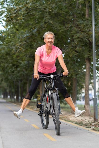 Smiley Senior Woman Avoir Un Bon Moment à Vélo à L'extérieur Photo gratuit