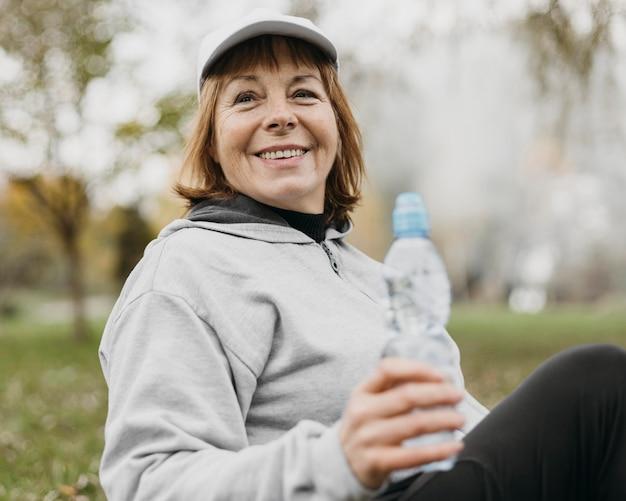 Smiley Senior Woman Eau Potable à L'extérieur Après Avoir Travaillé Photo gratuit