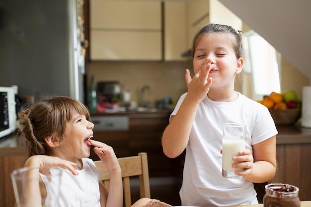 Smiley sœurs jouant en prenant son petit déjeuner Photo gratuit