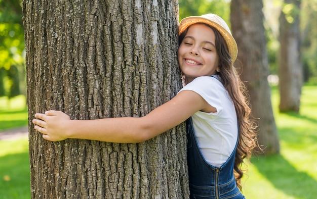 Smiley tir moyen petite fille embrassant un arbre Photo gratuit